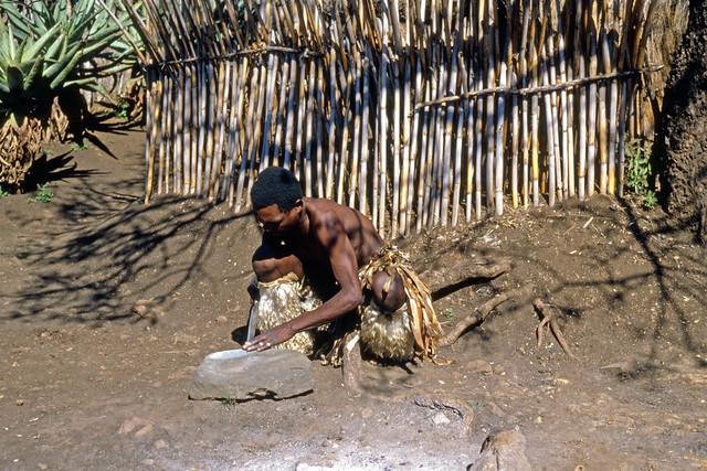 Young Zulu man sharpening knife on rock