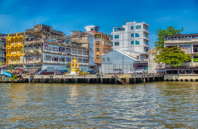 Houses and a shrine by the Chao Phraya river in Bangkok, Thailand