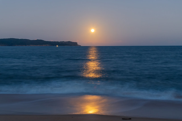 Pink supermoon and full moon rising over the sea