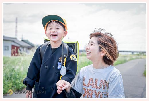 堤防で 制服姿の男の子とママ