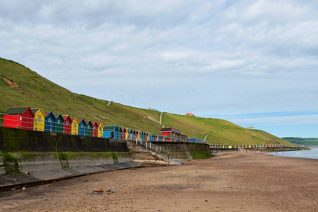 Multi-coloured beach huts on Whitby West Cliff, Whitby, North Yorkshire.