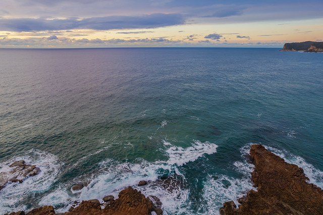 Aerial sunrise seascape with clouds and rock platform