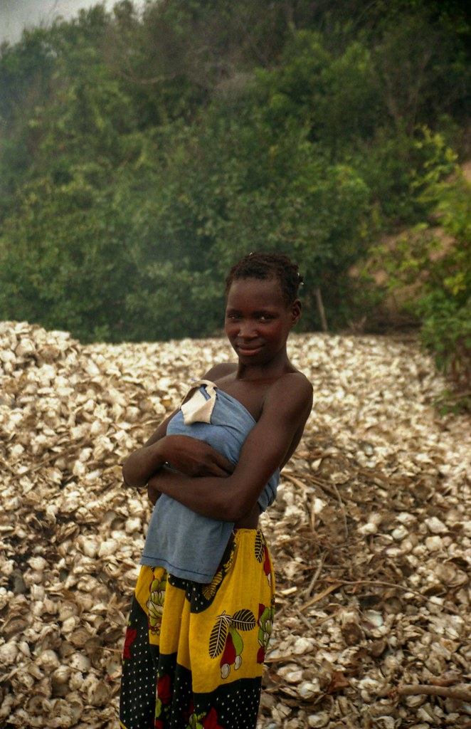 Girl with piles of oyster shells behind; near Vilanculos, Mozambique
