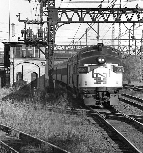 Penn Central ex New Haven Railroad EDER-5 class EMD FL-9 # 2027 is seen leading a late afternoon westbound passenger train past tower SS71 at Devon Junction and across a diamond while operating on a platform track at Devon, Connecticut, 1969