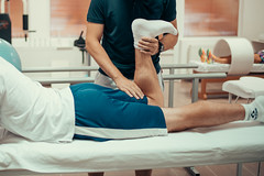 Physiotherapist working examining treating injured leg of male patient.