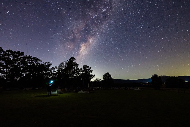 A rural cemetary with the stars and milky way sky shining brightly