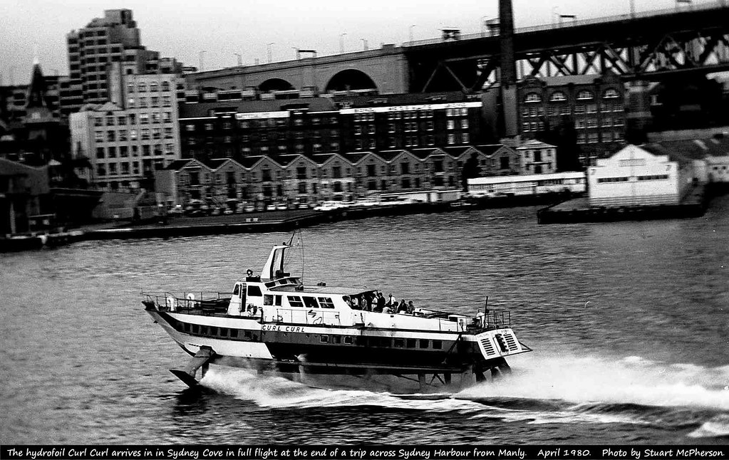 The hydrofoil Curl Curl arrives in Sydney Cove in full flight at the end of another 35-knot trip across Sydney Harbour from Manly (a speed that would be precluded in the 2020s by modern speed restrictions in force this part of Sydney Harbour).  Hydrofoils operated on Sydney Harbour between Circular Quay and Manly Wharf from 1965 until 1991.  At the time of this photo the NSW State Government operated a fleet of five in order to maintain (most of the time) a three-boat timetable between Circular Quay and Manly Wharf.  The fast 10 km trip - running in parallel to the traditional Manly Ferries - took 15 minutes all up.  Stuart McPherson photo.   April 1980.