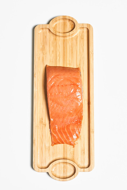 A piece of Red fish salmon meat on the long wooden plate