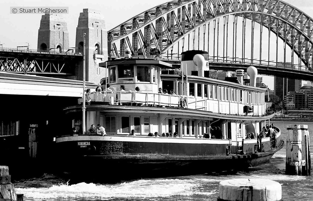 The magnificent 1912-built Sydney Harbour ferry Kanangra arrives @ Wharf 4 Circular Quay early during the year 1980 in a classic Sydney Harbour scene.  The historic and veteran Kanangra was built locally right here in Sydney by Mort's Dock Woolwich (near Hunter's Hill) before the First World War - and was one of dozens of her type constructed during this era to cater for Sydney's rapidly expanding public transport needs at the time.  Unlike most of the dozens of 'K Class' ferries of her type (names all began with the letter K), Kanangra's hull was of steel and not wooden construction.  She had a capacity a whisker under 1,000 passengers.  Originally a tall-funnelled coal-burning steam ferry, her boilers and reciprocating steam engine were removed and replaced in the late 1950s - and she was re-engined with a modern (for the time) Crossley 8-cylinder diesel.  She thus continued to operate on Sydney Harbour until the mid-1980s.  Kanangra's working career by the time of her 1985 retirement spanned a ridiculously-long 73 years.  When considering that a generally-anticipated lifespan for a steel ship is 25 or 30 years, this is a truly remarkable achievement for this Australian-built vessel (and her builders).  Fortuitously and wonderfully - Kanangra survives to this day at the grand old age of 109 years and is currently owned and under restoration by the Sydney Heritage Fleet - located in Sydney Harbour's Rozelle Bay.  It is intended that she ultimately be restored to full operating condition, and that we will one once again see this rare and truly magnificent vessel gracing Sydney Harbour.  Stuart McPherson photo.  March 1980.