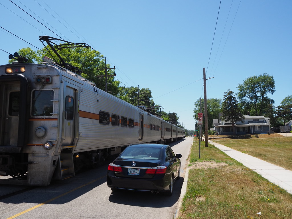 Car passing a South Shore Line train at 10th Street and Carlon Court