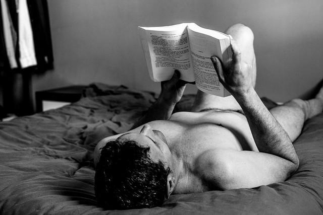 Aldéric en train de lire allongé sur le lit.