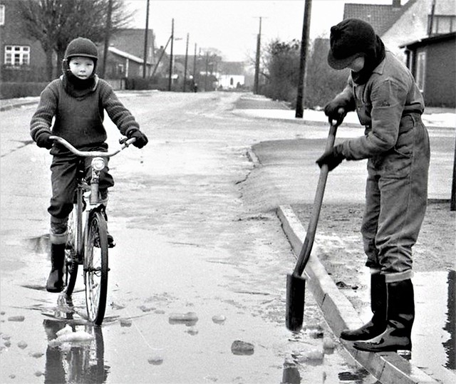 Flood, 1963. The two boys find it exciting to cycle through the water and make the water disappear through the sewer.