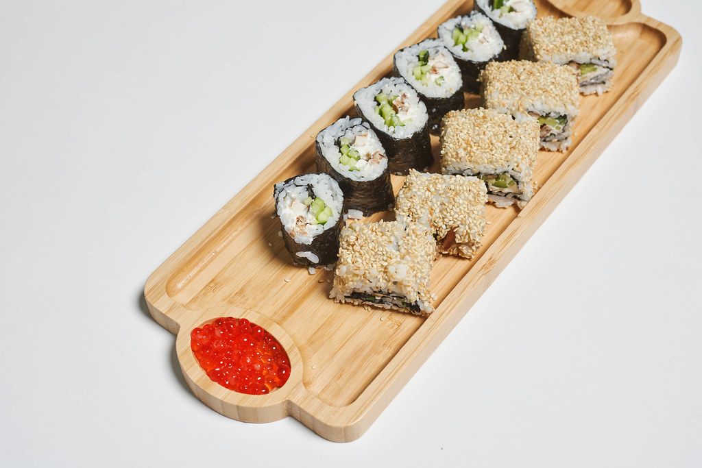 Portion of sushi served on wooden plate with red caviar
