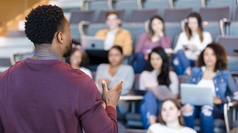 A male teacher gestures while giving a lecture to a group of university students.