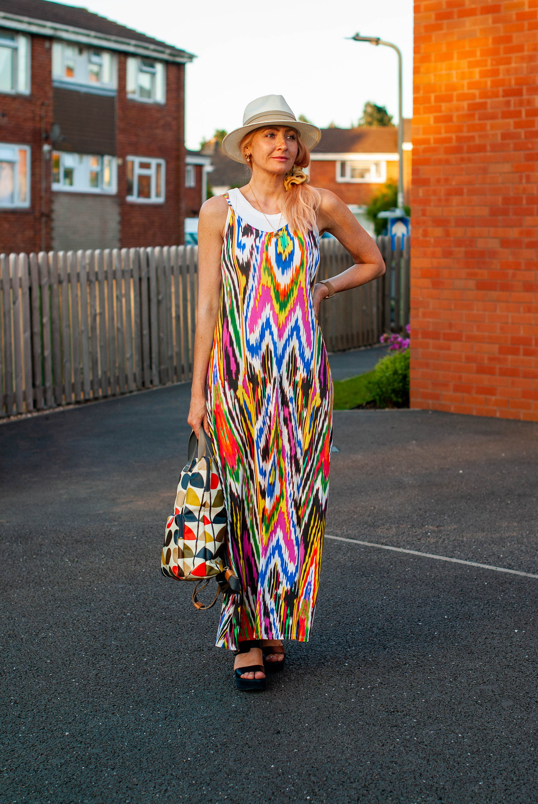 Layering a Rainbow-Explosion Maxi for Summer: Catherine Summers AKA Not Dressed As Lamb wearing an ikat-print multi-coloured maxi with white vest top, Panama hat, navy chunky sandals and an Orla Kiely backpack | Style over 40