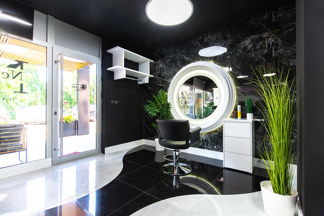 Beauty salon with beautiful mirror and green flowers decoration.