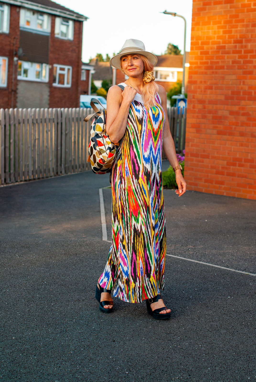 Layering a Rainbow-Explosion Maxi for Summer: Catherine Summers AKA Not Dressed As Lamb wearing an ikat-print multi-coloured maxi with white vest top, Panama hat, navy chunky sandals and an Orla Kiely backpack   Style over 40
