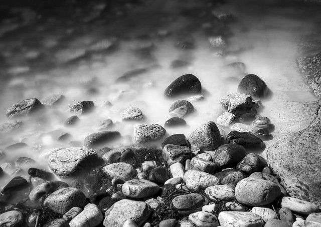 Water laps against rocks, Anstruther Harbour, Anstruther, Fife, Scotland, UK B&W