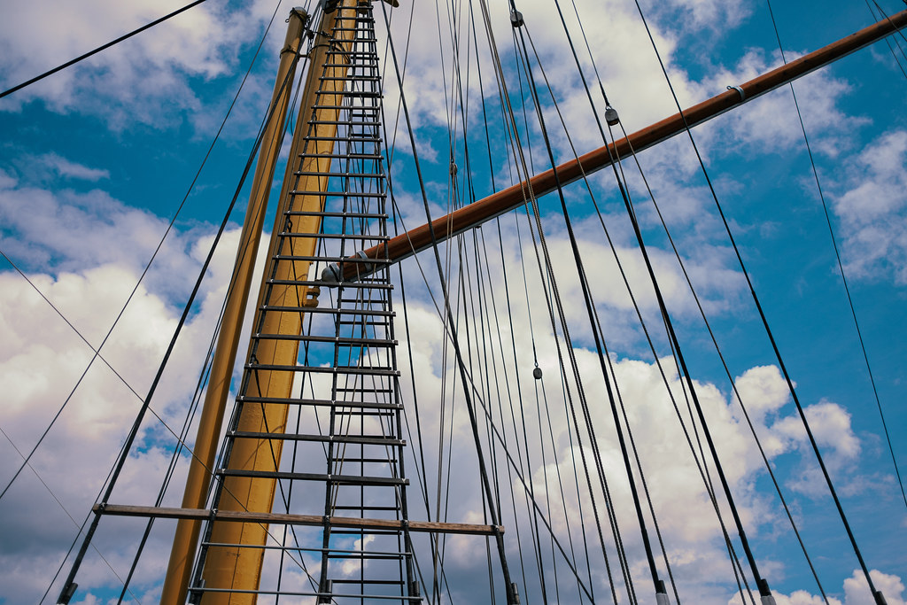 sailing mast with ropes in front of cloudy blue sky