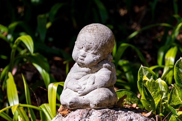 Novice doll statue in outdoor of public garden.