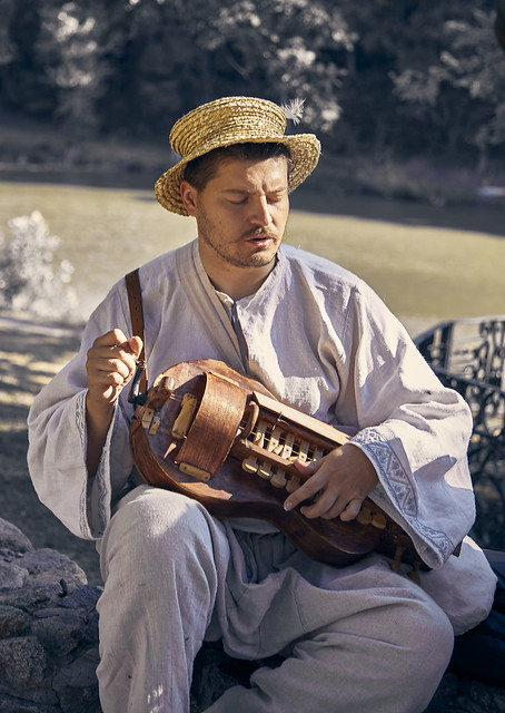 musician in national costume playing a wheeled lyre. The village of Skovorodinovka