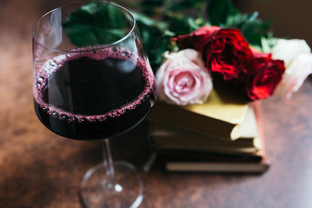 Red wine in a glass with roses and old books in background.