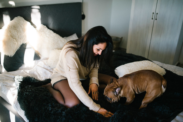 Attractive young woman in black tights have fun wit her dog in bedroom.