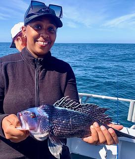 Photo of woman holding a black sea bass