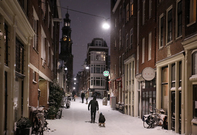 Father pulls son on sledge on a snowy evening in Amsterdam