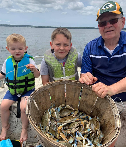 Photo of man and two boys with a basket of blue crabs