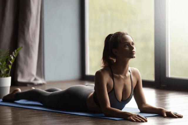 A-woman-performing-a-cobra-yoga-pose-e1575664007204
