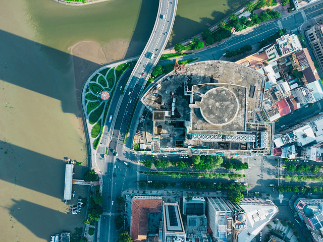 Bird View Drone Photo of the Rooftop of the unfinished and abandoned high-rise Building Saigon One Tower at the Saigon River next to Thu Ngu Flagpole in Ho Chi Minh City, Vietnam