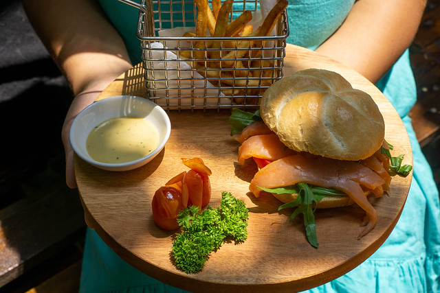 Person holding a Wooden Board with Smoked Salmon Sandwich with Arugula in a German Bread Roll, Honey Mustard Sauce, Tomatoes, Parsley and Homemade French Fries in a Basket