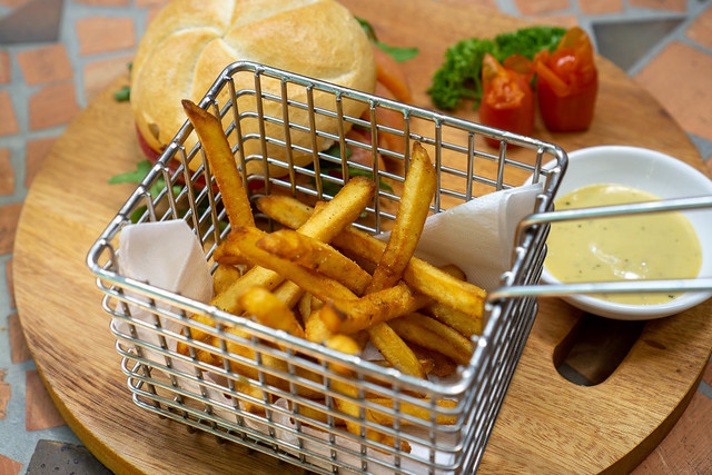 Close Up Food Photo of Homemade French Fries in a Metal Basket on a Wooden Tray with Smoked Salmon Sandwich and Honey Mustard Sauce in a Restaurant