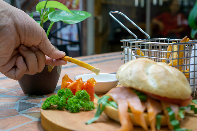 Close Up Food Photo of Person dipping French Fries in Honey Mustard Sauce with Smoked Salmon Sandwich on a Wooden Board in the Foreground