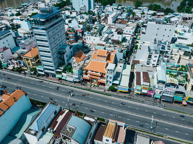 Aerial Drone Photo of a Buddhist Pagoda next to many Buildings along a Street with many Motorbikes in District 8 in Ho Chi Minh City, Vietnam
