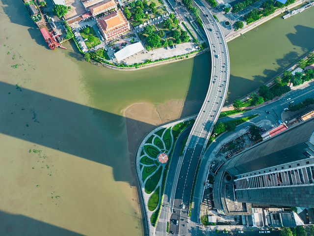 Top View Drone Photo of Thu Ngu Flagpole with Lotus Flower Park around it at the Saigon River and next to the unfinished Construction of Saigon One Tower in District 1 in Ho Chi Minh City, Vietnam