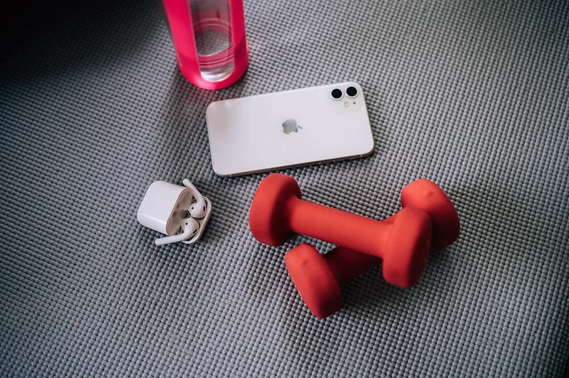 Close-up of two red dumbbells, AirPods, iPhone and a bottle of water on a yoga mat