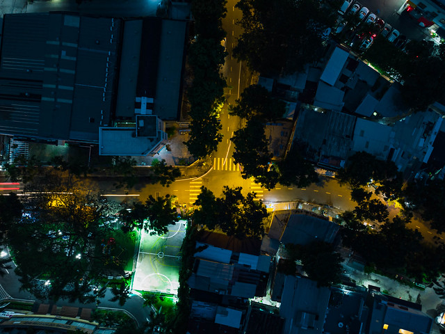 Long Exposure Top View Drone Photo of an Intersection in a local Neigborhood with Houses, Trees and a Football Field in District 4 in Ho Chi Minh City, Vietnam