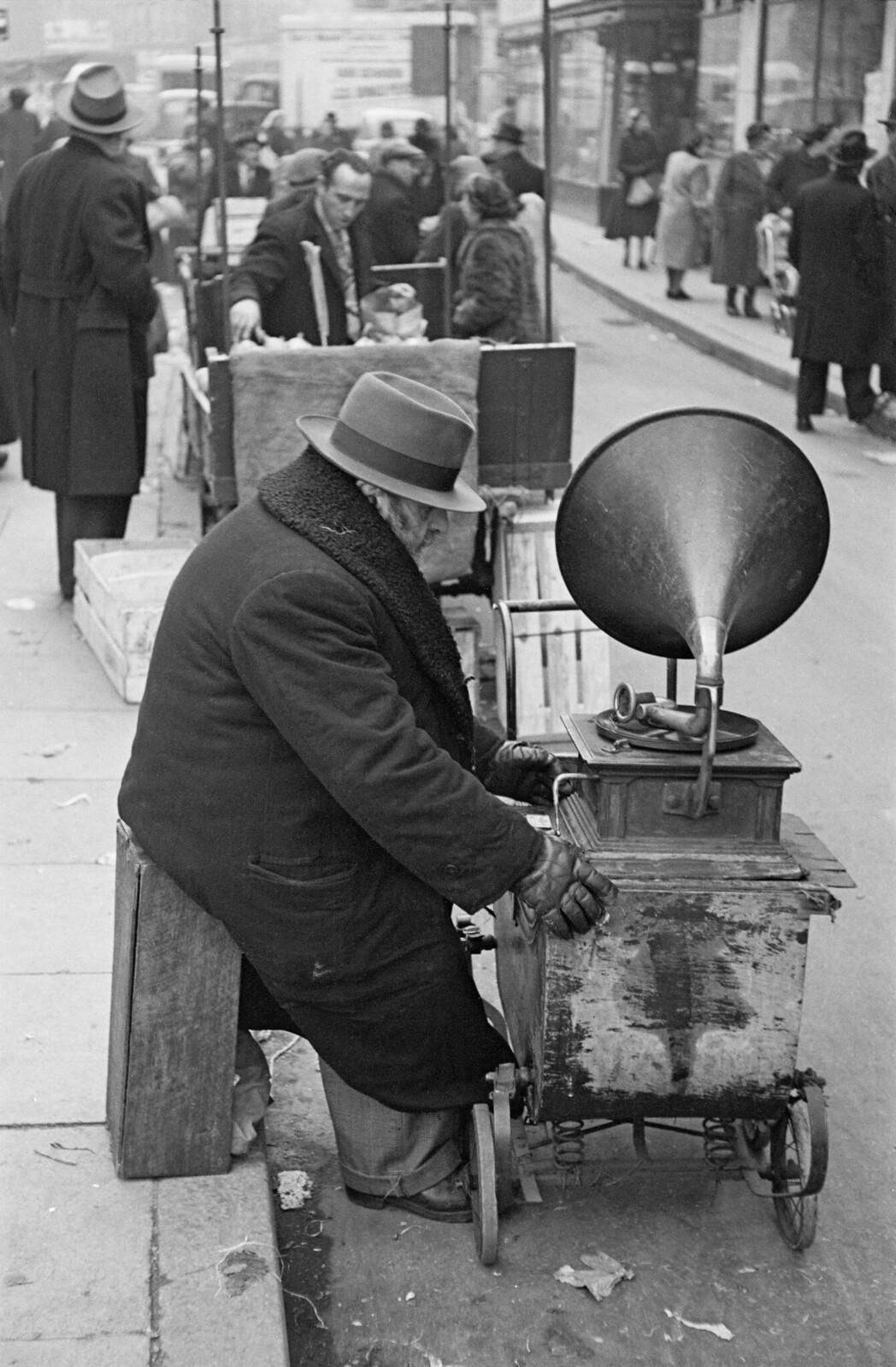 02. Еврей с граммофоном на колесах на уличном рынке в Уайтчепеле. Мужчина проигрывает старые пластинки, которые привез с собой из России, и собирает деньги в пользу беженцев в Израиль