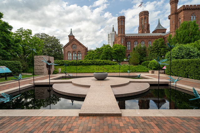 Washington, DC - May 9, 2019: The Moongate Garden with dragonfly statues in the Enid Haupt Garden and the Smithsonian Castle on the National Mall