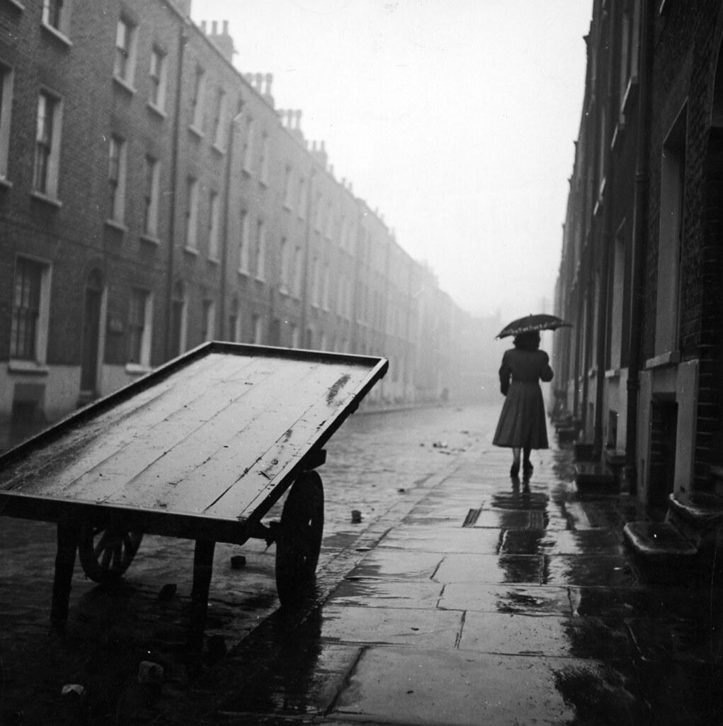 15. Женщина идет по дождливой улице в Уайтчепел