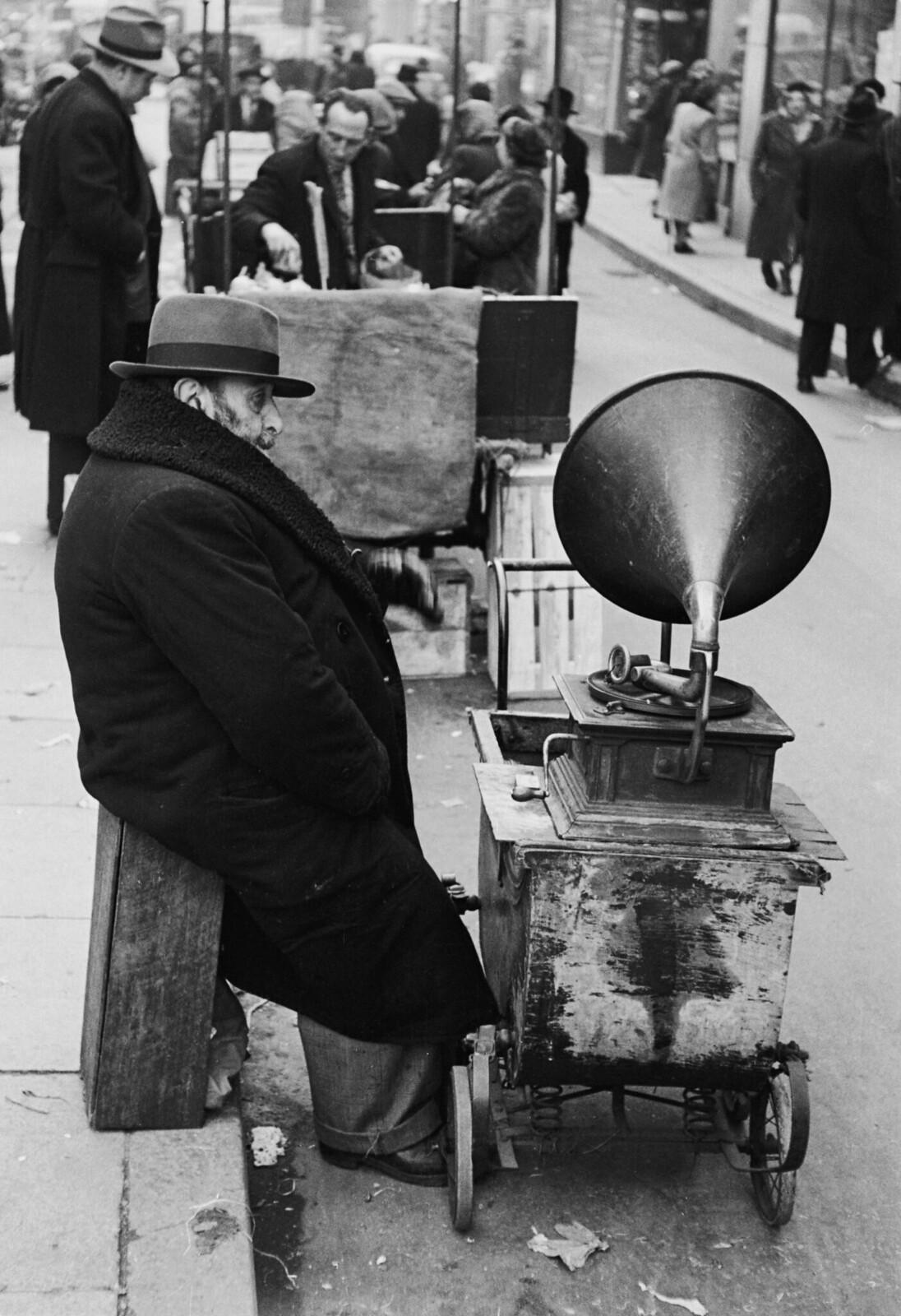 04. Еврей с граммофоном на колесах на уличном рынке в Уайтчепеле. Мужчина проигрывает старые пластинки, которые привез с собой из России, и собирает деньги в пользу беженцев в Израиль