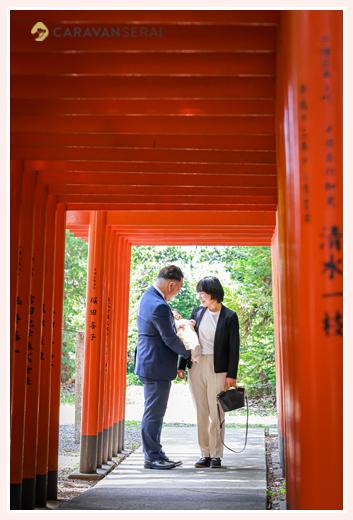 お宮参り 赤い鳥居で記念写真 ママとパパの服装はスーツ
