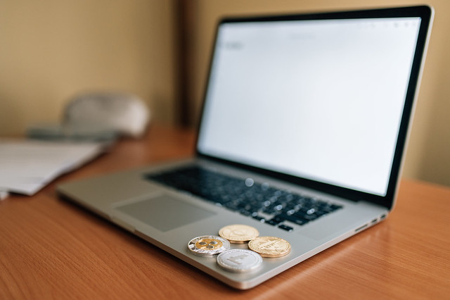 Physical Bitcoin, Ripple, Ethereum and Litecoin on the side of a laptop