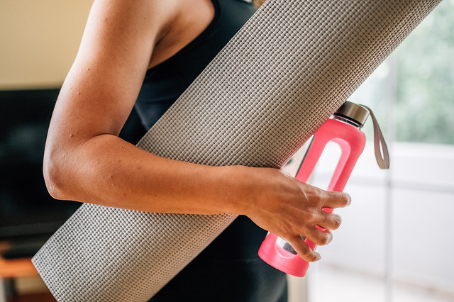 Close-up of a woman holding yoga mat and a bottle of water