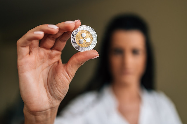 A female investor holding a physical Ripple coin