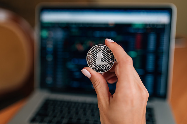 Close-up of a woman holding a physical Litecoin in front of a laptop