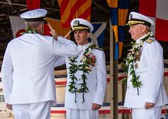 Rear Adm. Robert Chadwick, left, saluts Adm. Sam Paparo, commander of U.S. Pacific Fleet, when relinquishing command to Rear Adm. Timothy Kott, right during the CNRH/CNSGMP change of command ceremony. (U.S. Navy/MC2 Greg Hall)