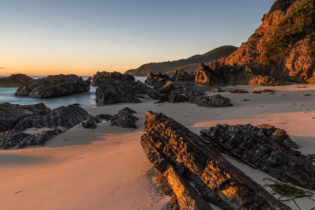 Sunrise seascape and a rocky beach softly lit by sunlight